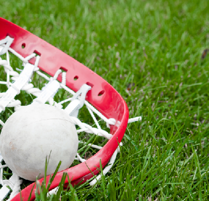 Lacrosse stick and ball on field