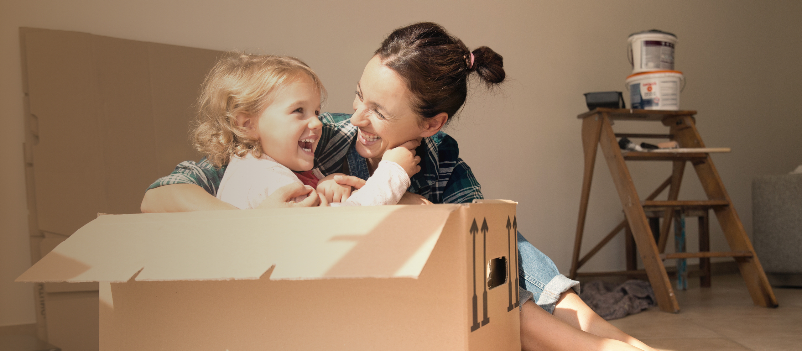 woman playing with little girl in a moving box