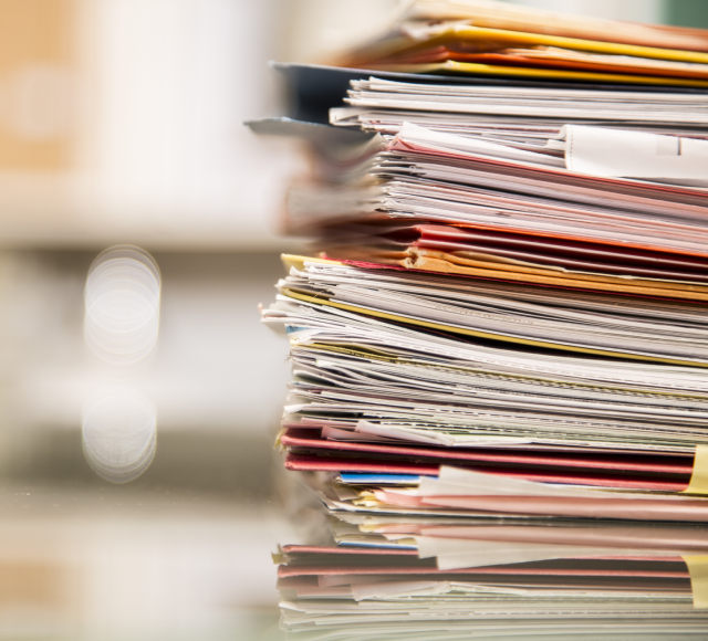 stacks of office files cluttering desk
